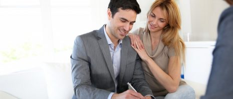 A couple signing a document from a real estate lawyer