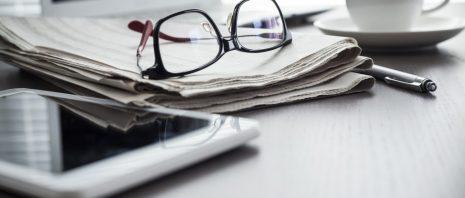 Newspaper and tablet on desk