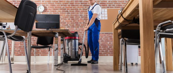 Male janitor cleaning office