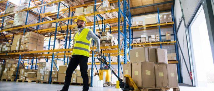 Man pulling pallet truck in warehouse