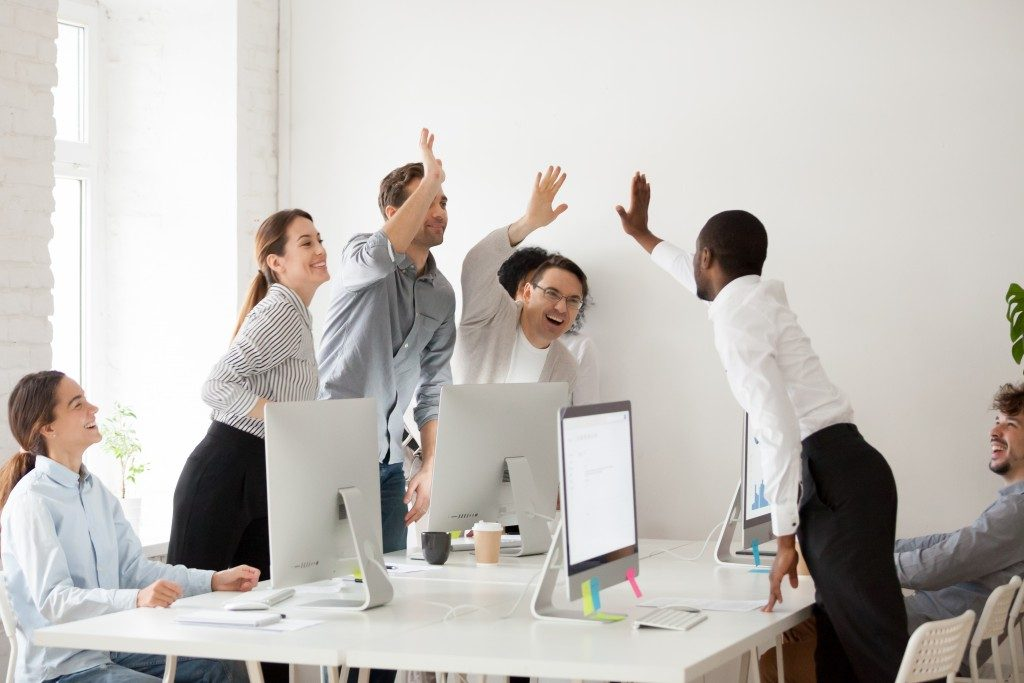 Happy employees giving each other high fives
